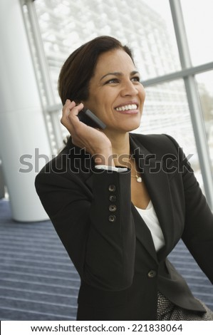 Hispanic businesswoman talking on cell phone - stock photo