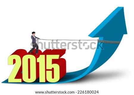 Hispanic businesswoman with number 2015 draws upward arrow - stock photo