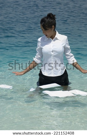 Hispanic businesswoman with papers in water - stock photo