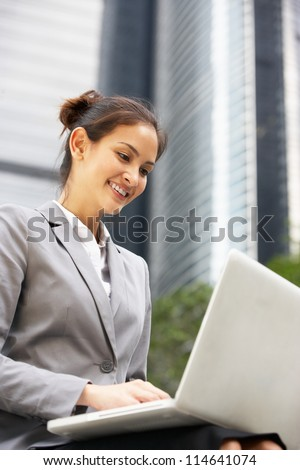 Hispanic Businesswoman Working On Laptop Outside Office