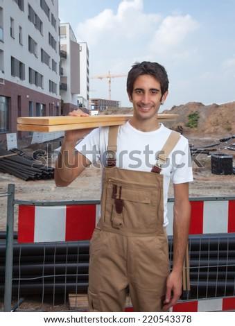 Hispanic carpenter on construction site - stock photo