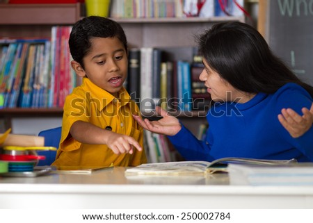 Hispanic Child  Reading with Mother