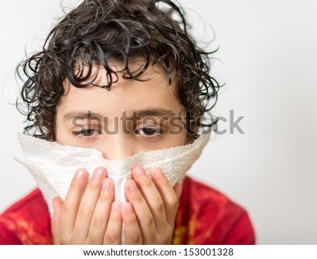 Hispanic child with curly hair suffering from the flu. Kid blowing his nose. Seasonal virus caught by a 7 years old child. He is kept out of school for a few days. - stock photo