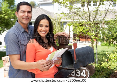 Hispanic Couple Checking Mailbox - stock photo