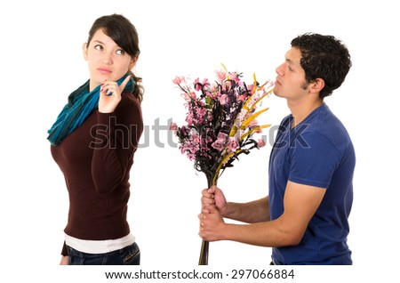 Hispanic couple fighting as man attempts to give girlfriend flowers but she gives him cold shoulder attitude looking backwards with finger up in air. - stock photo