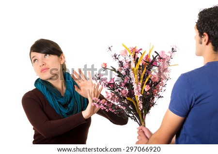 Hispanic couple fighting as man tries to give girlfriend flowers while she pushes them away with annoyed facial expression. - stock photo