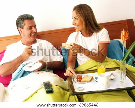 Hispanic couple having breakfast at bed. - stock photo