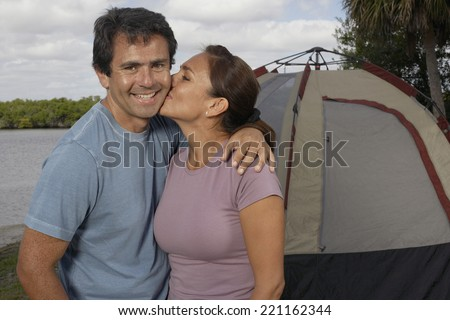 Hispanic couple in front of tent - stock photo