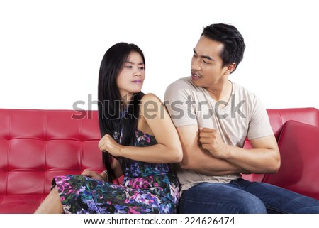 Hispanic couple quarreling on couch and looking with hate to each other  - stock photo