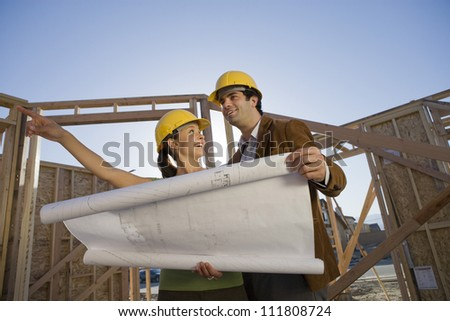 Hispanic couple reviewing blueprint at construction site