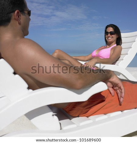 Hispanic couple smiling at each other at beach - stock photo