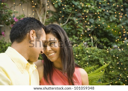 Hispanic couple smiling at each other outdoors - stock photo