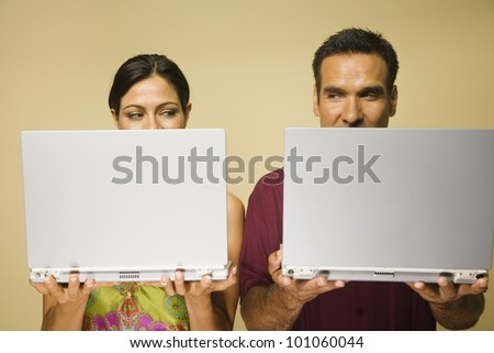 Hispanic couple standing next to each other holding laptops - stock photo