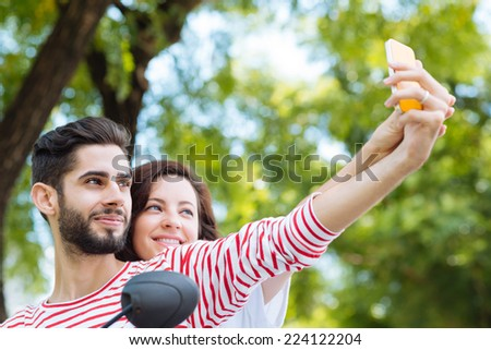 Hispanic couple taking selfie while sitting on the scooter - stock photo