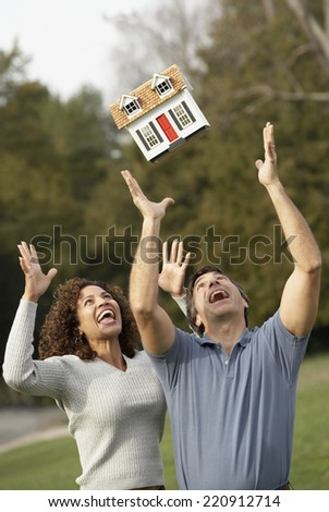 Hispanic couple throwing model of house in air - stock photo