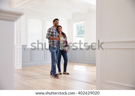 Hispanic Couple Viewing Potential New Home - stock photo