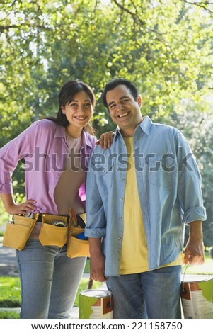Hispanic couple with tool belt and paint cans - stock photo