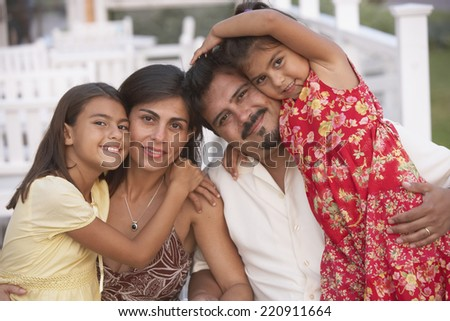 Hispanic family hugging on porch - stock photo