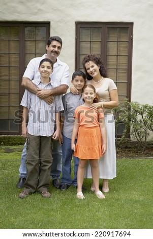 Hispanic family in front of house - stock photo