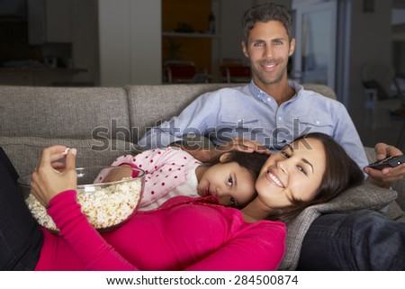 Hispanic Family On Sofa Watching TV And Eating Popcorn - stock photo