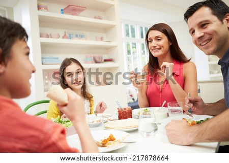 Hispanic Family Sitting At Table Eating Meal Together - stock photo