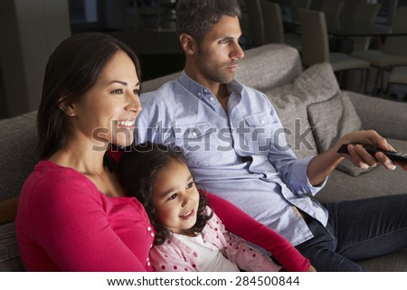 Hispanic Family Sitting On Sofa And Watching TV - stock photo