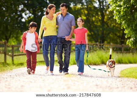 Hispanic Family Taking Dog For Walk In Countryside - stock photo
