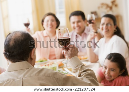 Hispanic family toasting at dinner table - stock photo