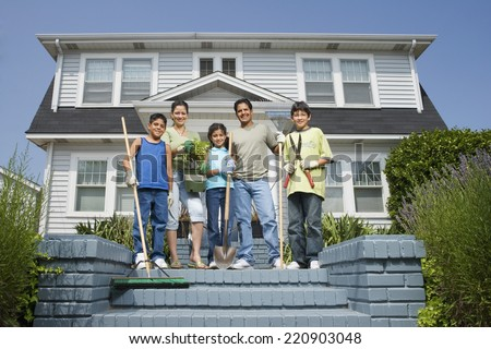 Hispanic family with gardening tools in front of house - stock photo