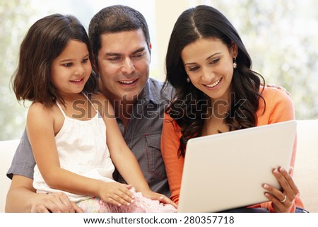 Hispanic family with laptop at home - stock photo