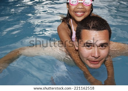 Hispanic father and daughter in swimming pool - stock photo