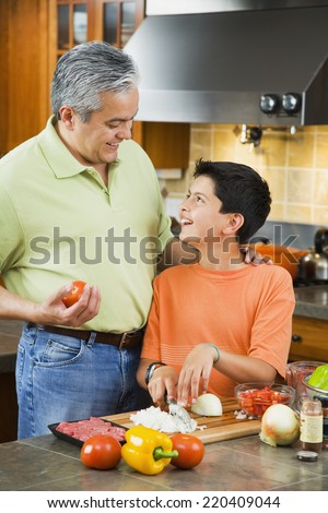 Hispanic father and son chopping vegetables in kitchen - stock photo