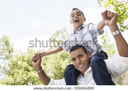 Hispanic Father and Son Having Fun Together Riding on Dad's Back in the Park. - stock photo