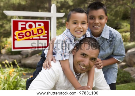 Hispanic Father and Sons in Front of a Sold Home For Sale Real Estate Sign. - stock photo