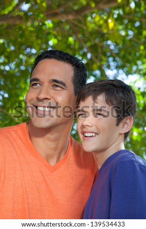 Hispanic father and teenaged son happily standing together outside in yard, looking off into distance.