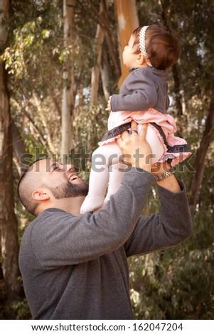Hispanic father holding beautiful baby girl - stock photo