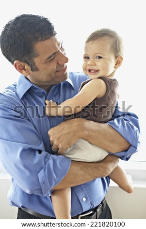 Hispanic father holding daughter - stock photo