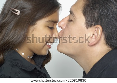 Hispanic father kissing daughter's nose