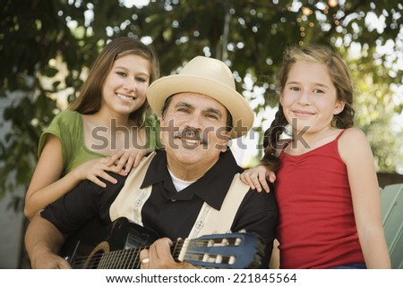 Hispanic father playing guitar for daughters - stock photo