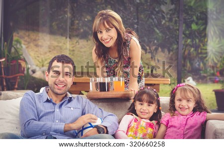 Hispanic father sitting in sofa with two daughters and mother leaning over from behind serving tray of drinks, garden background. - stock photo