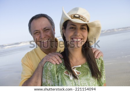 Hispanic father with hands on daughter's shoulders - stock photo
