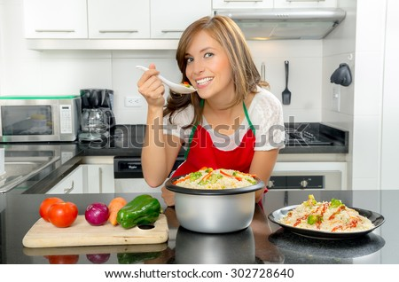 Hispanic female in modern kitchen holding spoon with food to mouth and smiling towards camera. - stock photo