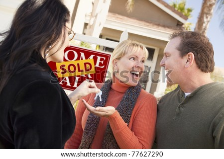 Hispanic Female Real Estate Agent Handing Over New House Keys to Excited Couple. - stock photo