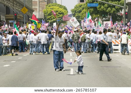 Hispanic girl and father with American flag watch hundreds of thousands of immigrants participating in march for Immigrants and Mexicans protesting Illegal Immigration  Los Angeles, CA, May 1, 2006