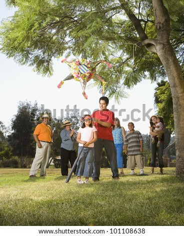 Hispanic girl being blindfolded next to pinata - stock photo