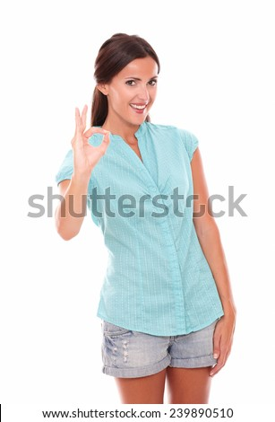 Hispanic girl in blue blouse gesturing a great job while looking at you and smiling in white background - stock photo