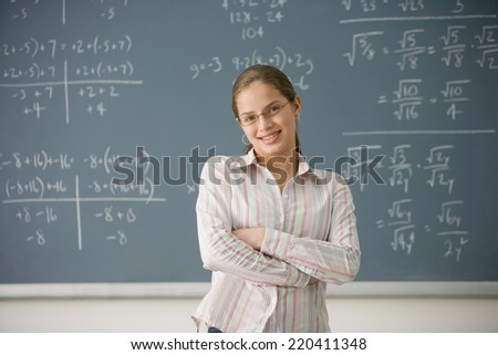 Hispanic girl next to blackboard with math problems - stock photo