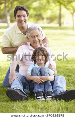 Hispanic Grandfather, Father And Son Relaxing In Park - stock photo