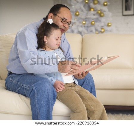 Hispanic grandfather reading to granddaughter - stock photo