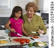 Hispanic grandmother and granddaughter preparing food - stock photo